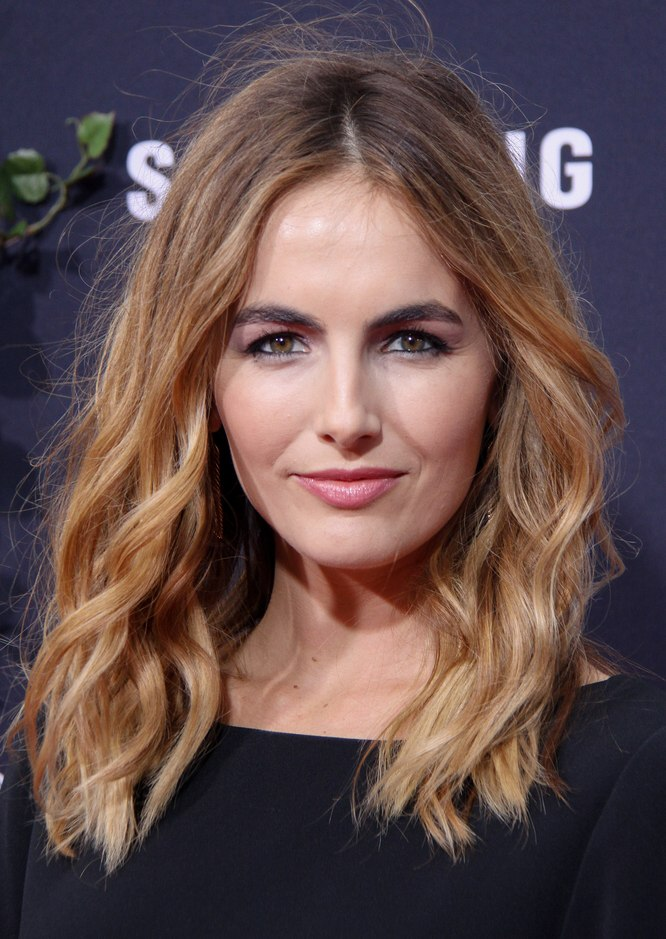 Camilla Belle wearing her hair wavy with a middle part