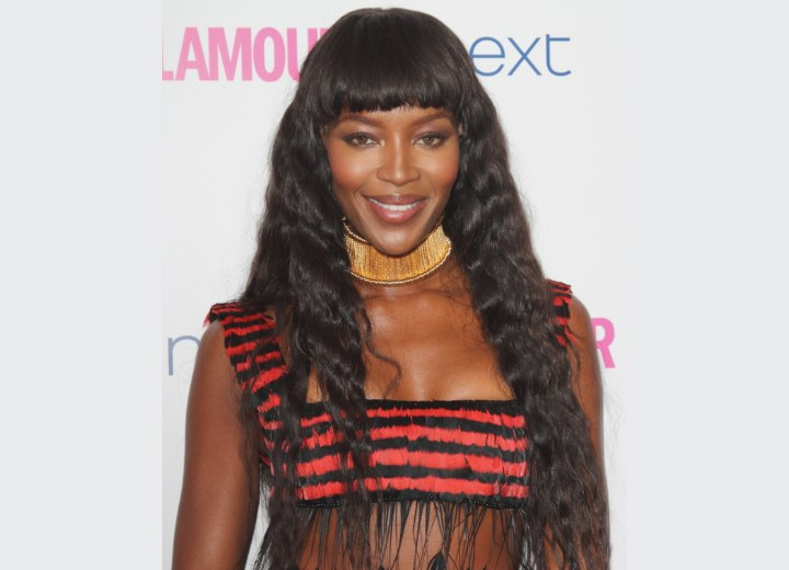 Naomi Campbell with her long hair styled in small waves