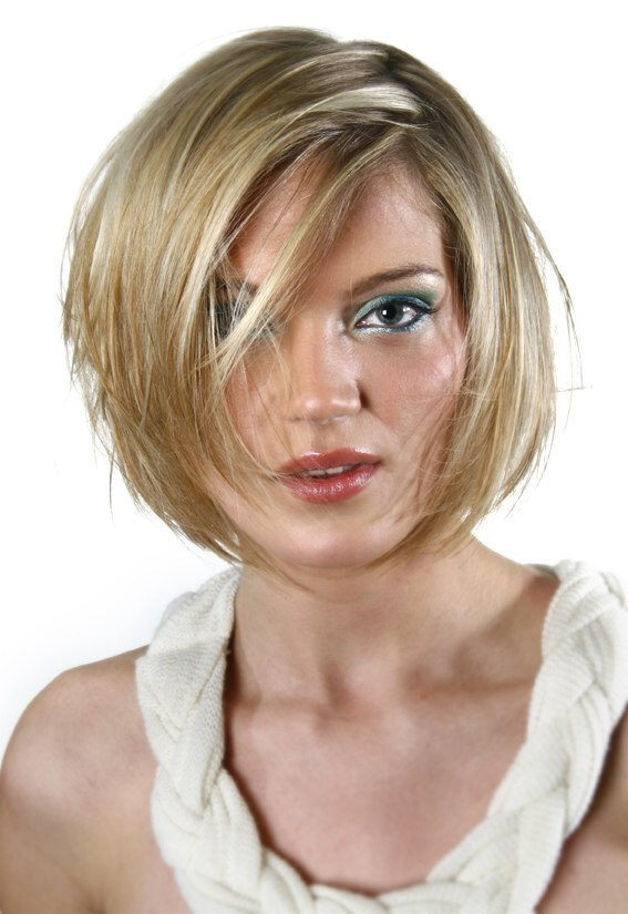 Short bob hairstyle with an irregular side part and strands of hair over the face