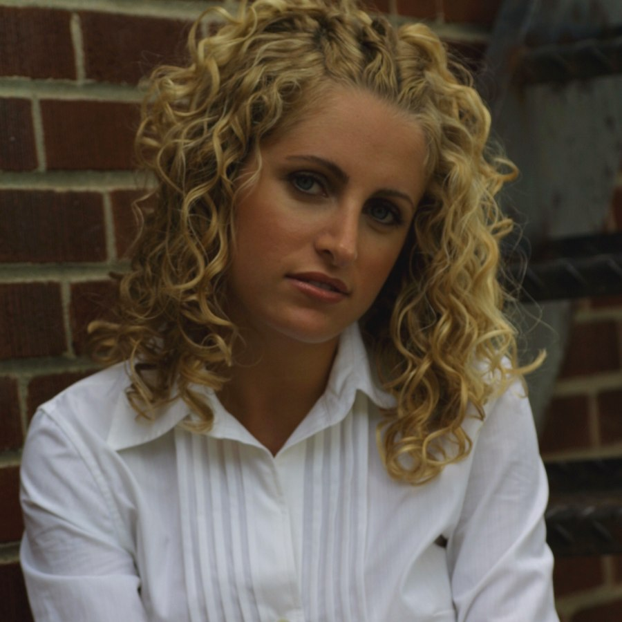 Hairstyle With Curls And Twirled Back Bangs