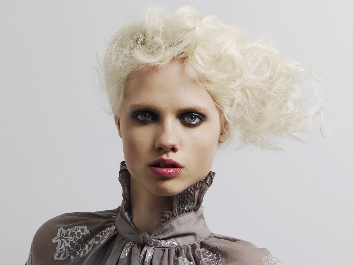 Milky-blonde hair styled with soft high-volume curl or a platform of ...