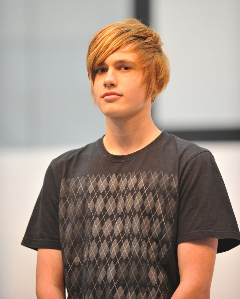 Young Man With Short Blonde Hair And Forward Swept Strands For A Face Hugging Hairstyle
