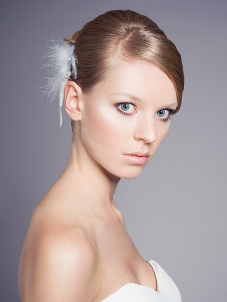 Updo with a chignon and a feathery hair accent