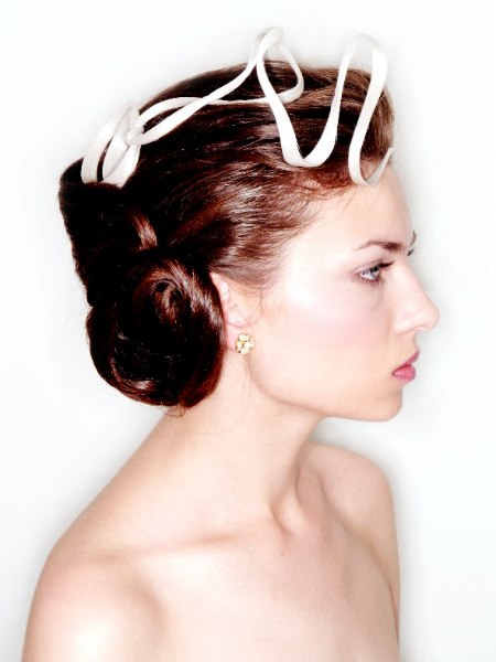 Classic up do with a sleek roll in the back and a satin ribbon