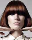 Sleek chin length bob with long bangs and the ends curved inwards
