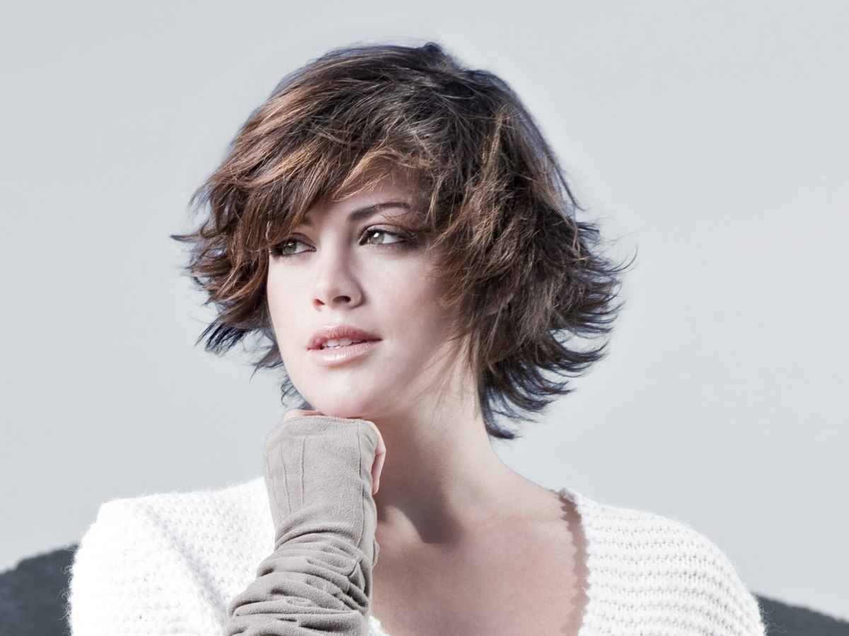 Short Layered Haircut With Movement And Bangs Curved Across The Forehead
