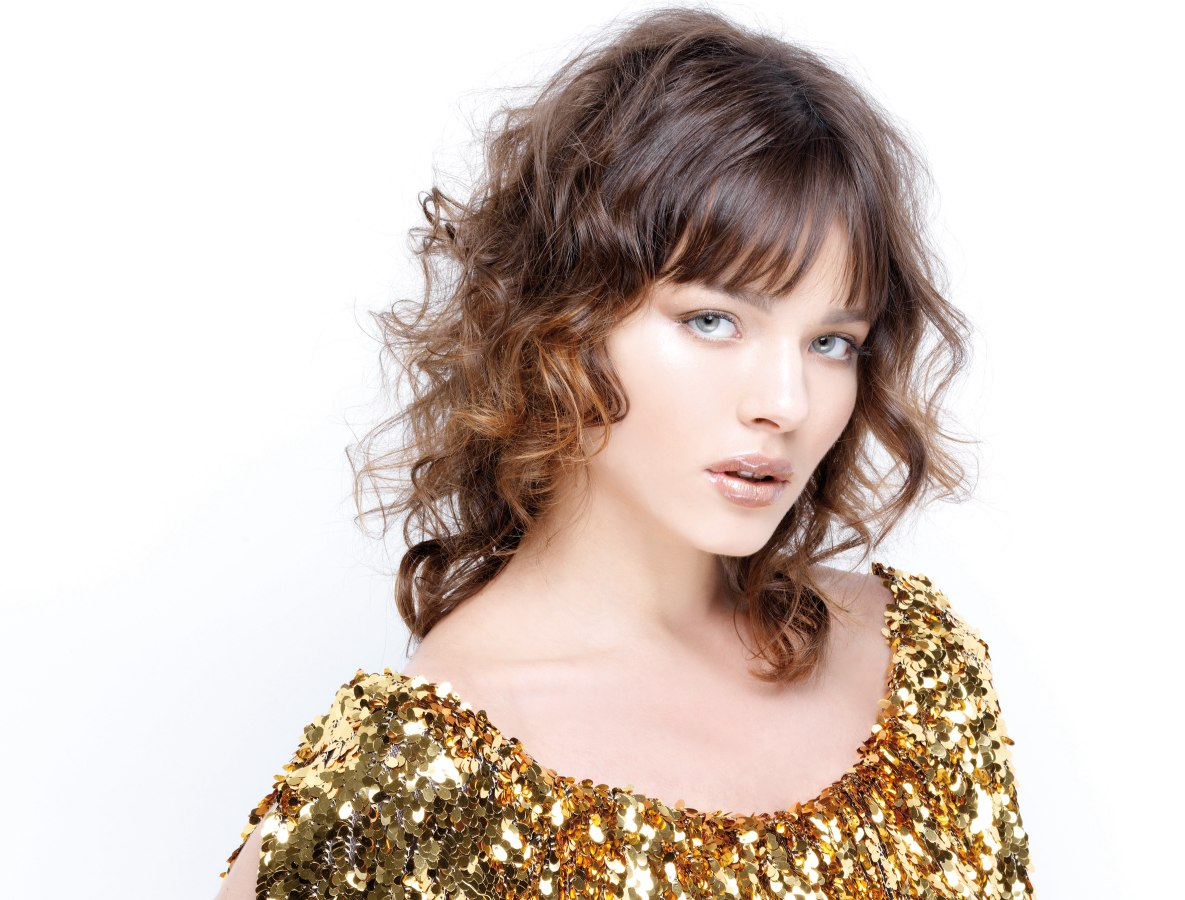 Modern Hairstyle With Curls And Straight Brow Length Bangs