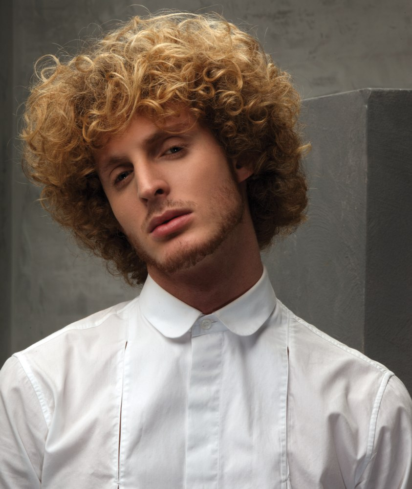 Layered men's hairstyle with curls and a long fringe
