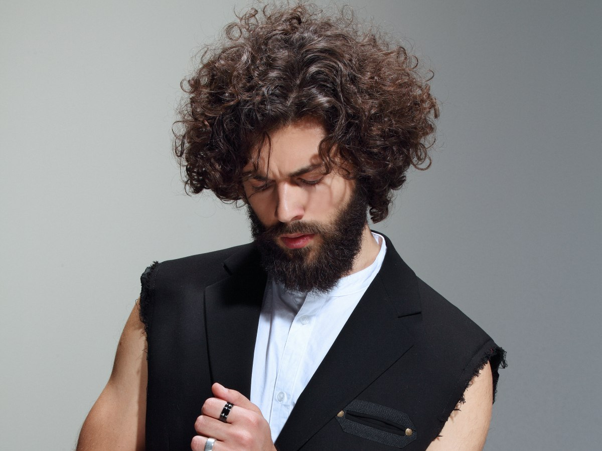 men's hairstyle with long curls and a full beard
