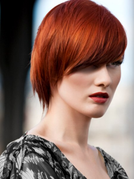 Short Textured Haircut With Diagonal Styling Bright Red Hair Color