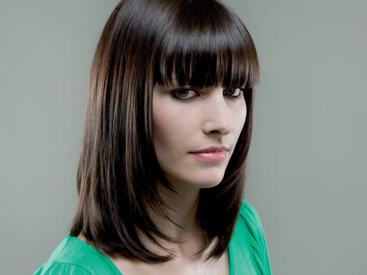 medium long face framing hairstyle with brow covering bangs to